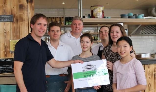Personeel van de BioExpress reikt de prijs uit aan Team Sushi-burger.