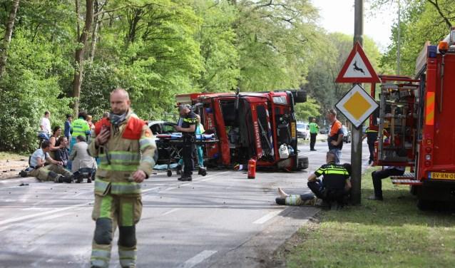 De gecrashte brandweerwagen. Een aantal gewonden zit in de bermen.