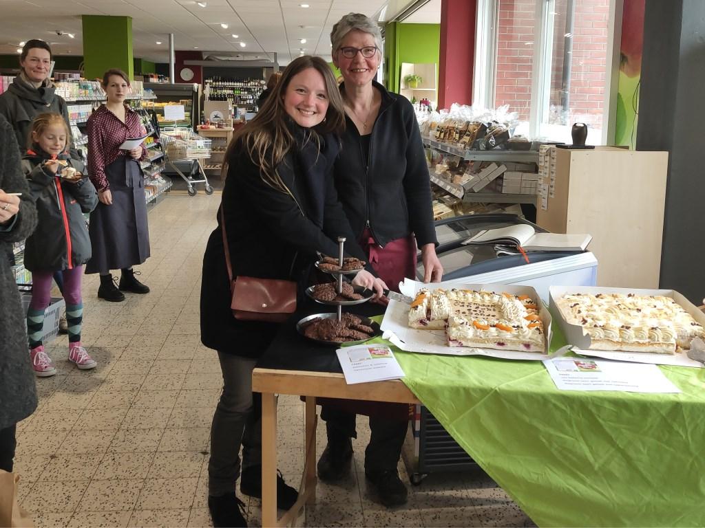 Logo-ontwerpster Krista Wamsteker (l) en Toos Verdouw snijden de taart aan.