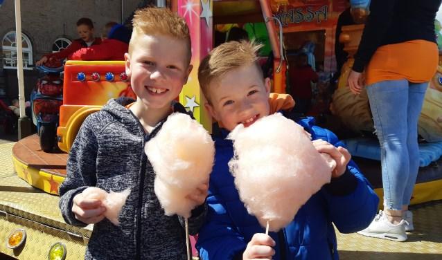 Twee jongens genieten van hun gratis oranje suikerspin.