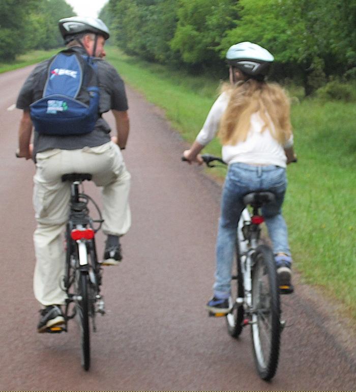 Ouder en kind fietsen samen.