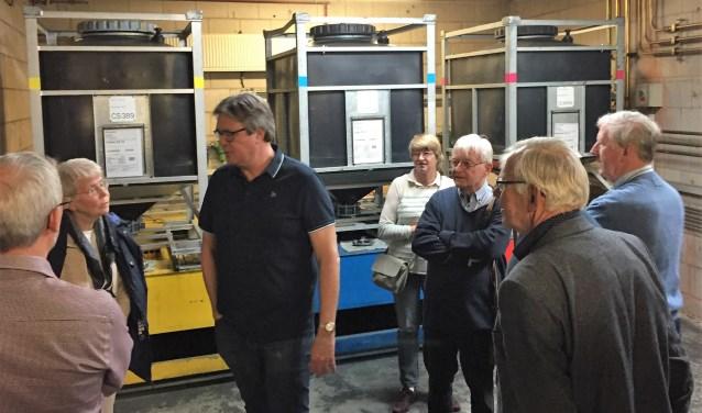 Daan Bleuel (BDU) geeft uitleg over het drukproces, met op de achtergrond 'inktcartridges' van 1000 liter per kleur.
