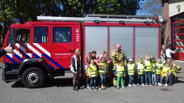 De kinderen met jufs bij de brandweerwagen