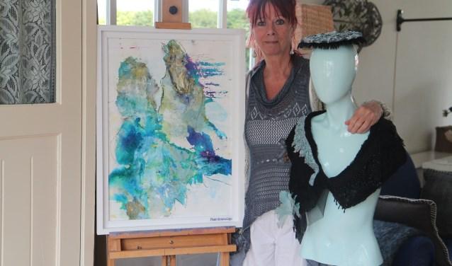 Nelleke Droog met één van haar schilderijen en een paspop met kraag en hoedje.