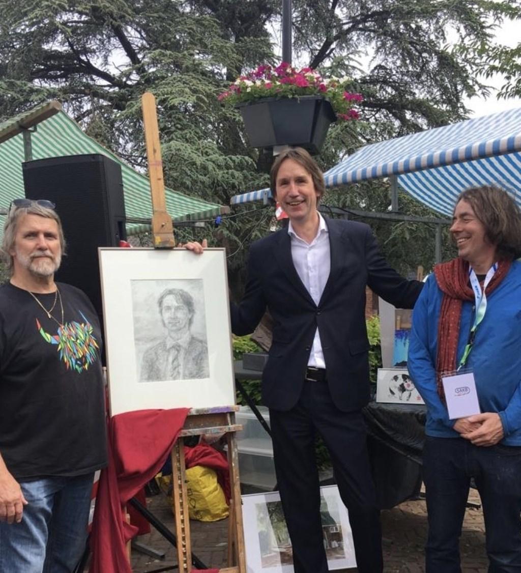 Wethouder Herbert Raat neemt het door Edgar Jansen gemaakte portret in ontvangst. Eigen foto © BDU media