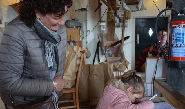 Mila tekent het gastenboek in de molen