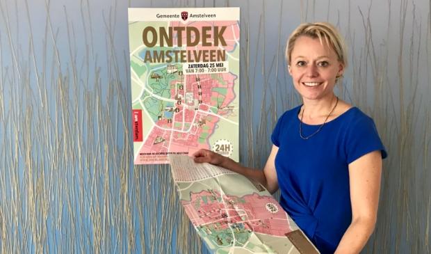 <p>Wethouder Floor Gordon bij de poster van de eerste editie van 24H Amstelveen. Het 24 uur durende programma krijgt in september een tweede editie.</p>