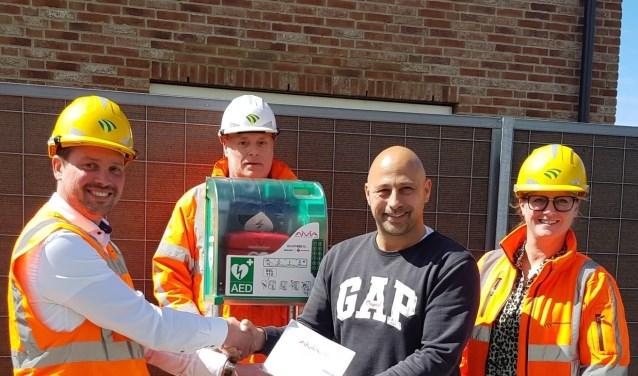 v.l.n.r. Bedrijfsleider Jeroen Turenhout, Gebiedsassistent Fred Heisterkamp en Omgevingsmanager Leontien Benders overhandigen namens DURA Vermeer de 1e Buurt AED van Tudorpark aan initiatiefnemer Harry Schuit.