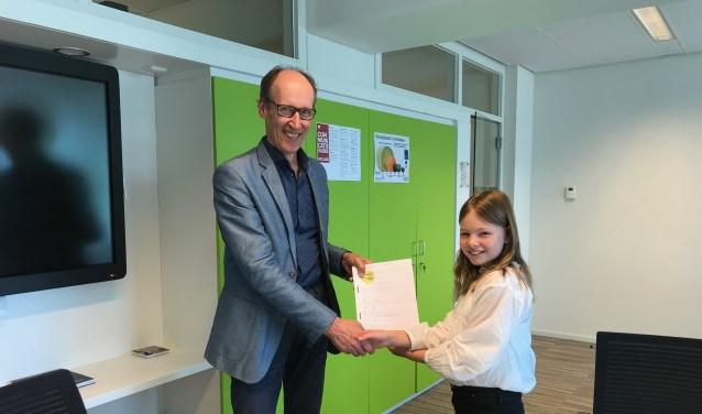 Wethouder Hoefsloot krijgt de handtekeningen uit handen van Sterre Overbeeke.