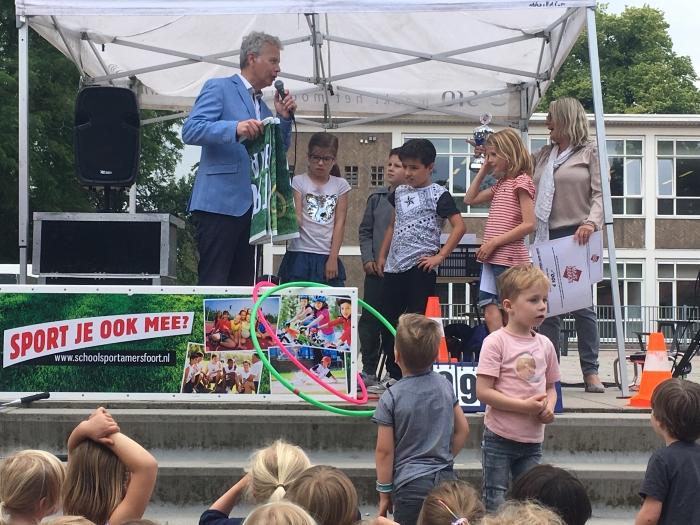 Wethouder Buijtelaar reikt de prijs uit aan enkele leerlingen van de Joost van den Vondelschool