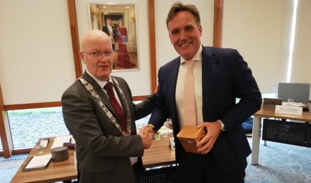 Burgemeester overhandigt Eijbersen een horloge op zonneenergie