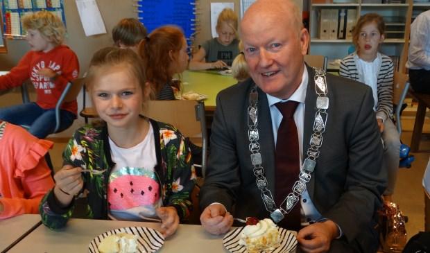 Beide burgemeesters samen aan de taart
