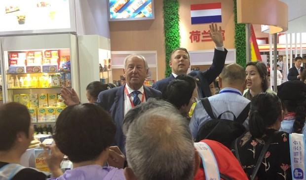 Gerard van den Tweel (midden): ,,De Chinezen blijken gek te zijn op de typisch Nederlandse producten die wij uitdeelden.'' Rechts achter hem collega Cees van der Poel uit Dordrecht.
