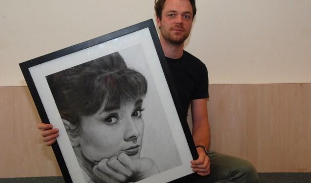Martijn Versteeg met een portret van Audrey Hepburn.