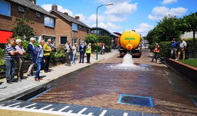 Belangstellenden, waaronder burgemeester Naafs (midden), zagen dat het nieuwe afwateringssysteem prima werkt.