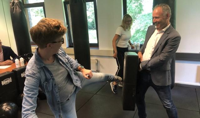 Buurtsportcoach Sandra van Ravenhorst leert Wethouder Patrick Kiel de basisbeginselen van een bokszaktraining.