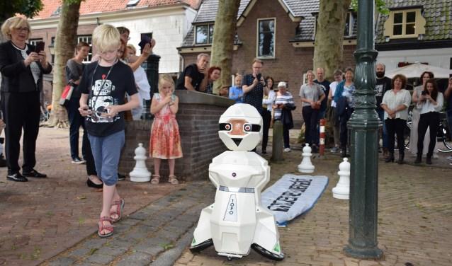 Kleinzoon Lars zet robot Topo aan het werk