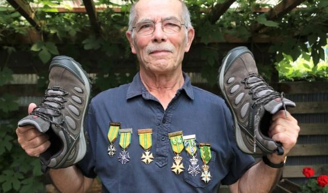 """Marcel Vermaas in de tuin met zijn medailles en wandelschoenen. ,,Elk jaar ben ik uitgeput na de Vierdaagse en zeg ik dat ik niet meer mee doe. Maar in het volgend voorjaar krijg ik de kriebels en ga ik toch weer trainen."""""""