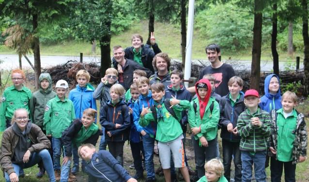Een enthousiaste groep Jongenswelpen met leiding voor hun vertrek naar hun zomerkamp in Breda.