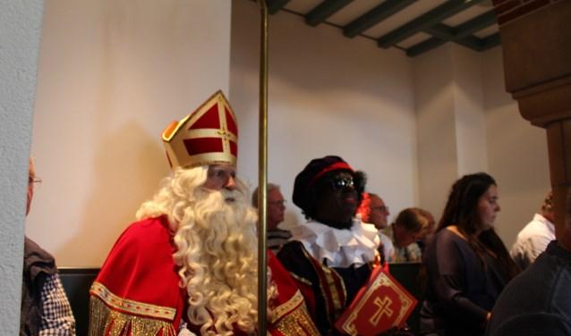 Sinterkaas en zijn hoofdpiet op de publieke tribune in de raadszaal tijdens het debat over subsidie voor het Sinterklaasfeest.