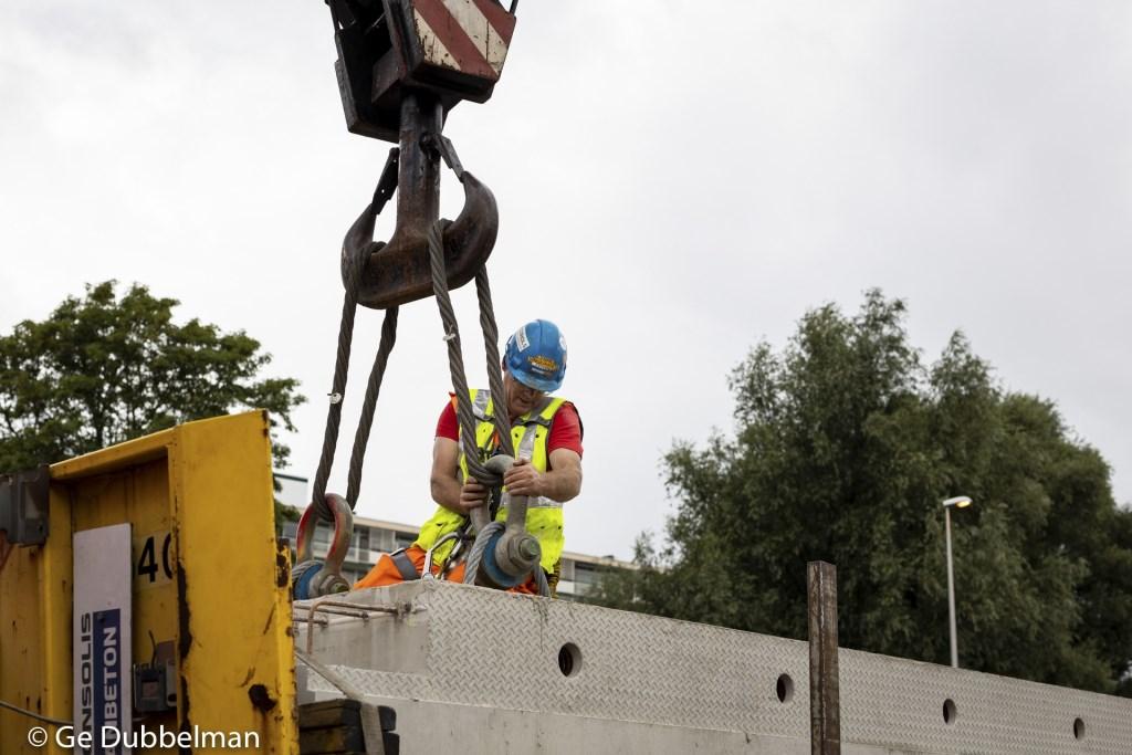 Het voorbereiden van het inhijsen van een betonnen ligger voor het toekomstige wegdek van het kruispunt Kronenburg. Ge Dubbelman © BDU media