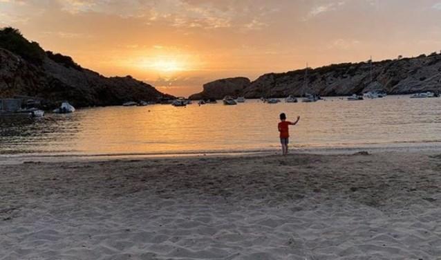 De kleinzoon van Anja Klomp geniet van de zonsondergang op het strand van Ibiza.