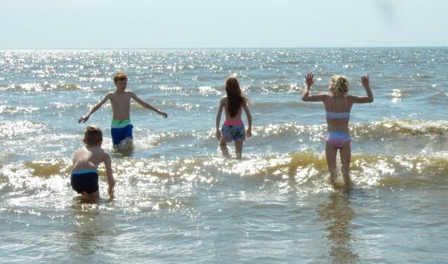 De kleinkinderen van Joly van der Steldt - Zev, Nova, Jesse en Isabelle - spelen bij IJmuiden in zee.