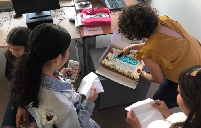 Docent en leerlingen van Haarlem College snijden Numo-taart aan.