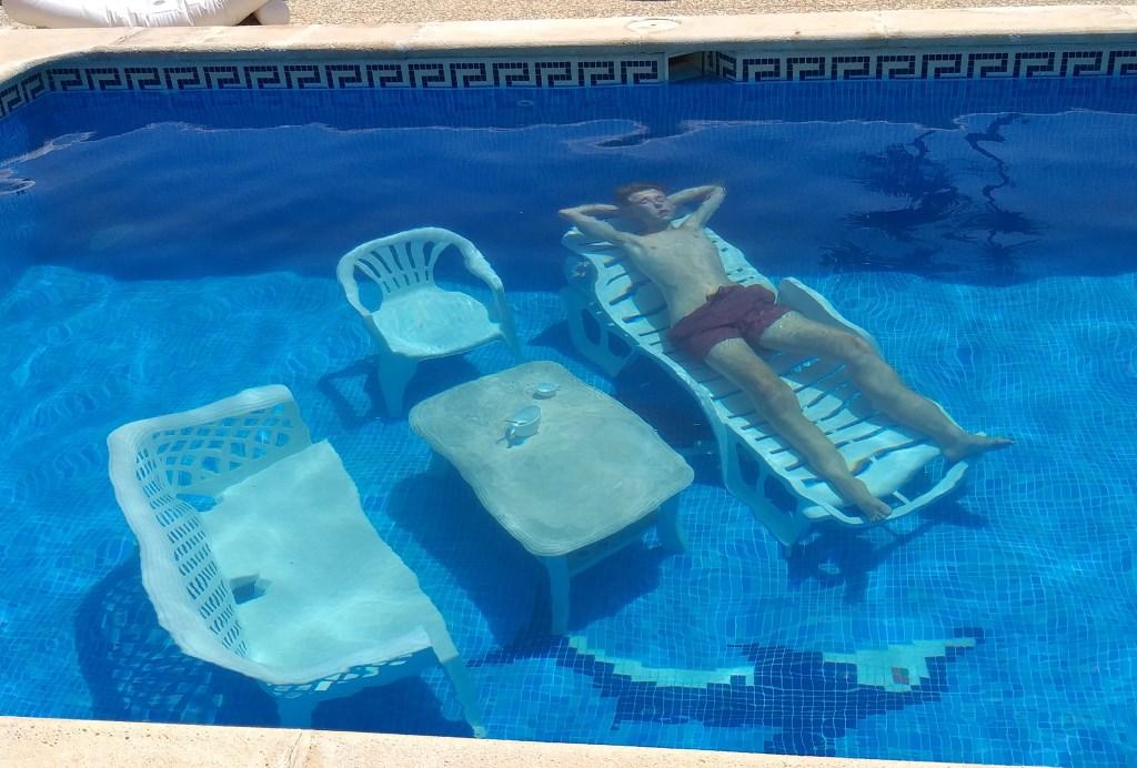 Siem Kooistra uit Zwartebroek haalde alles uit de kast voor de zomerfotowedstrijd. Op de bodem van het zwembad van een vakantieverblijf in Ariata (dichtbij Sevilla) richtte hij een compleet terras in. ,,Ik had de tuinmeubels in het water gegooid en ging daar vervolgens op liggen. Ik had ook twee kopjes op de tafel gezet.'' Kooistra © BDU media