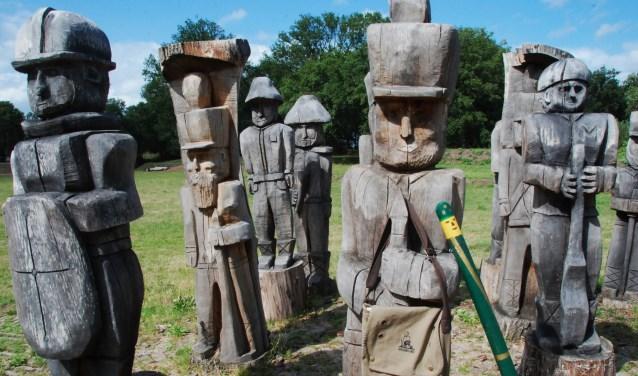Een houten soldaat met in z'n hand de tas met opdrachten en het paaltjes, zoals die langs de route voor de jeugd te vinden is.