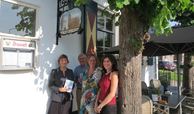 Wethouder Erika Spil (links) ontvangt het eerste exemplaar van de gids uit handen van Irene Okkerman (rechts). In het midden Piet Koning en Yvon Hoogendijk van het comité.