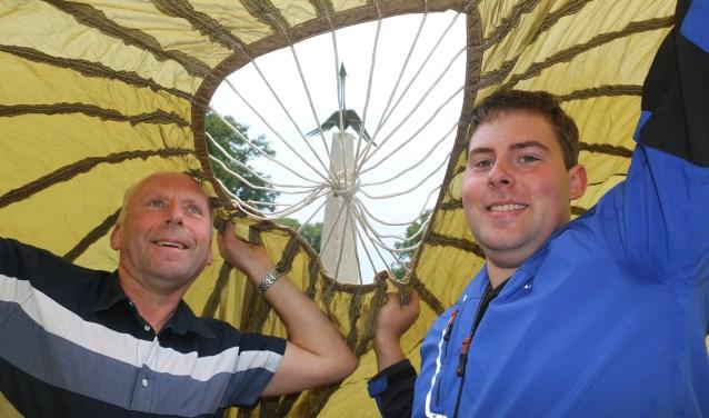 Vader Kees en zoon Remco onder het doek met zicht op het monument met de vogel.