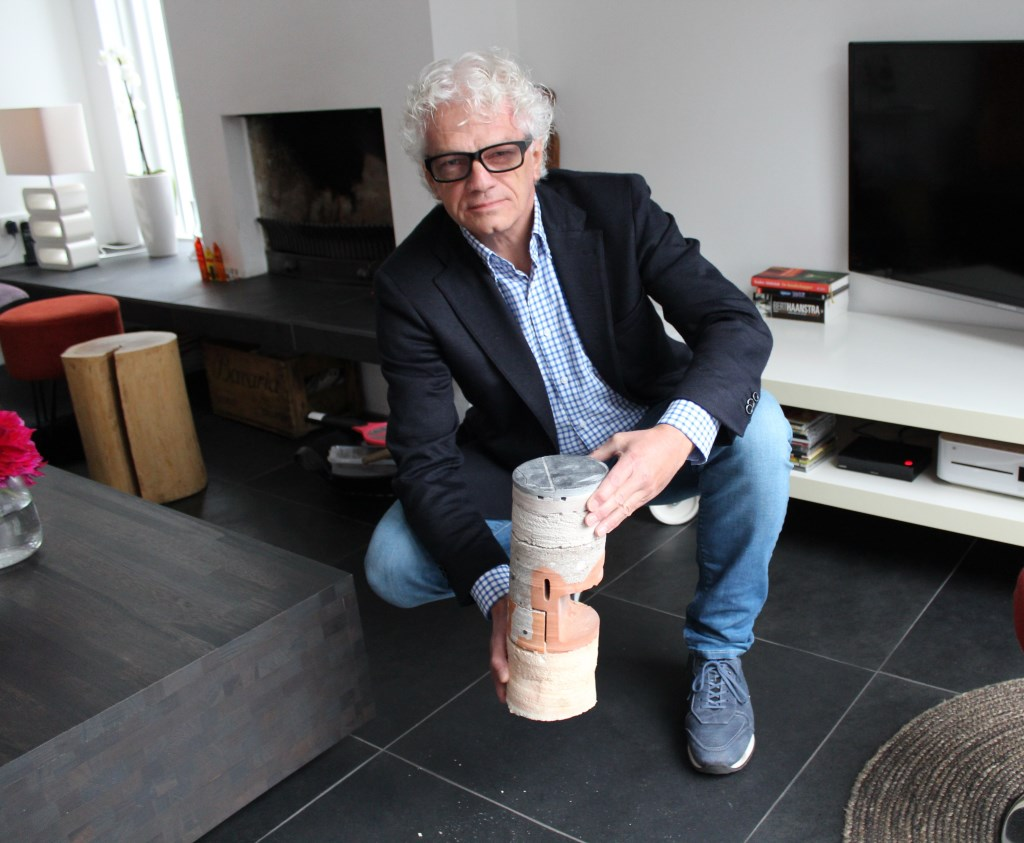 Wim Nijboer laat een doorsnede zien van de geïsoleerde vloer onder hem.