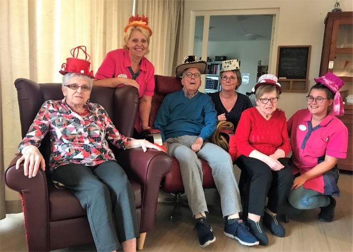 Bewoners van een afdeling kleinschalig wonen poseren met hoed samen met Bea Stooker en een mantelzorger.