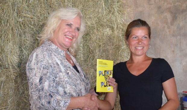Wethouder Wil Kosterman krijgt de brochure overhandigd door Walenka Broskiwiets