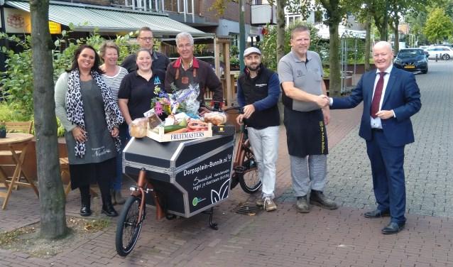 De sleutel van de elektrische bakfiets wordt overhandigd aan de winkeliers van Dorpsplein-bunnik.nl