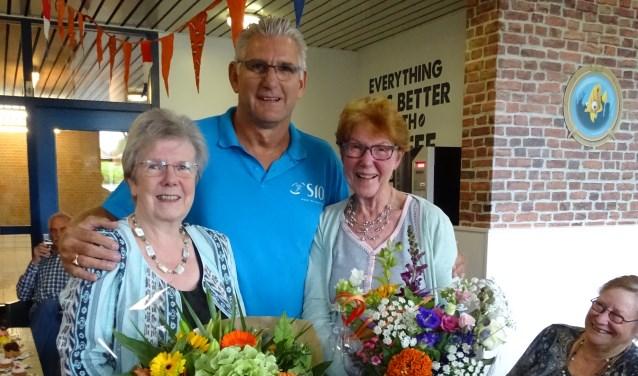 De twee jubilarissen Lijda Oudenes en Alij Grammé omarmt door Silvester Claassen