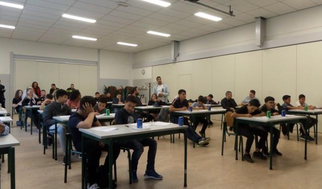 De deelnemers aan het DOCK Dictee der Nederlandse Straattaal doen hun best om vijfendertig vragen goed te beantwoorden.
