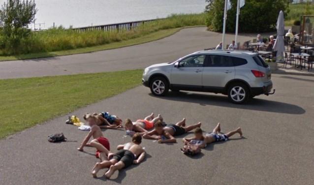 Een groep jongens ligt op het asfalt langs de Tooelnburgerplas.