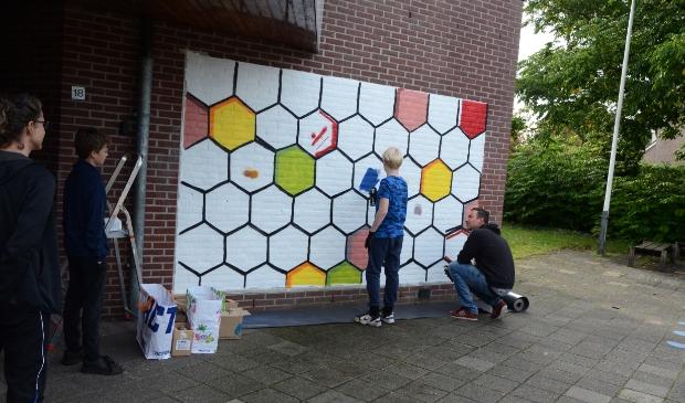Onder leiding van street-art artiest Daniël van de Haterd maken Leusdense jongeren een fraaie afbeelding op de gevel van 'De Smederij'.