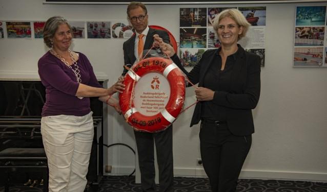 Koen Breedveld, directeur Reddingsbrigade Nederland, overhandigt een cadeau aan Jannechien Peek en burgemeester Nienhuis.