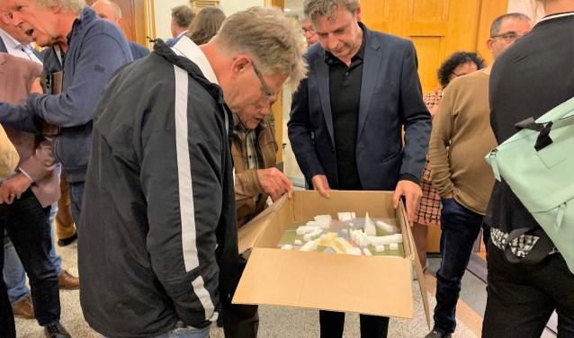 Het publiek buigt zich over de maquette na afloop van de infoavond in het gemeentehuis.