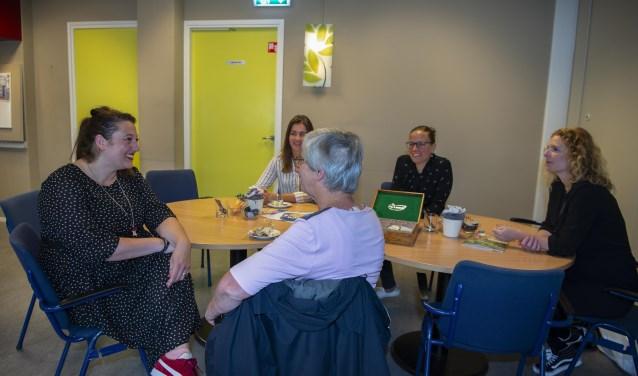 Mevrouw Jansen (midden) in gesprek met het team van De Buurttafel