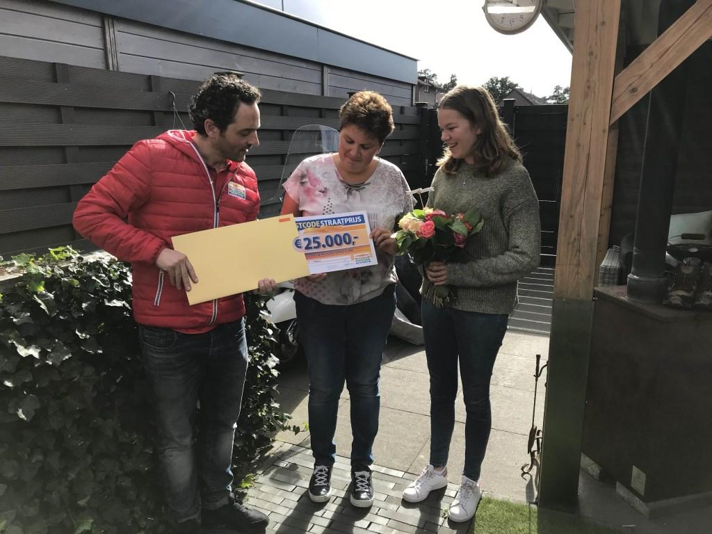Echtgenote en dochter van winnaar Jan uit Wekerom worden verrast door de Postcode Loterij met de PostcodeStraatprijs-cheque.
