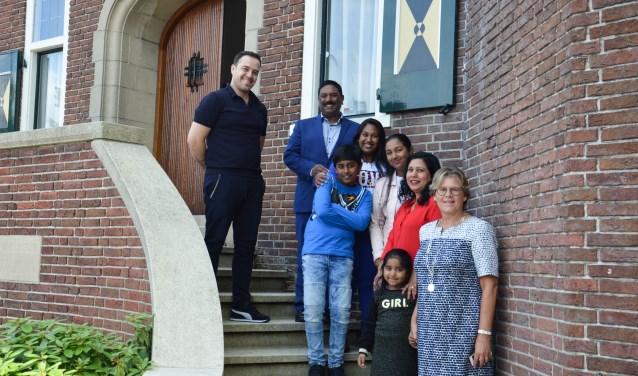 Burgemeester Cnossen voor het gemeentehuis met zeven nieuwe Nederlanders.