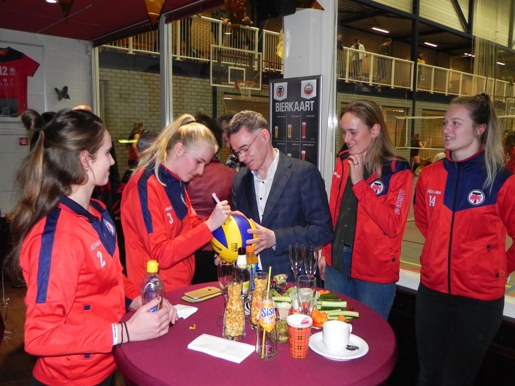 Burgemeester Gilbert Isabella laat zijn bal signeren door alle speelsters van dames-1. Richard Thoolen © BDU media