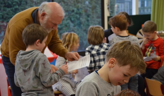 Jan Overweel bekijkt het werk van een van de leerlingen