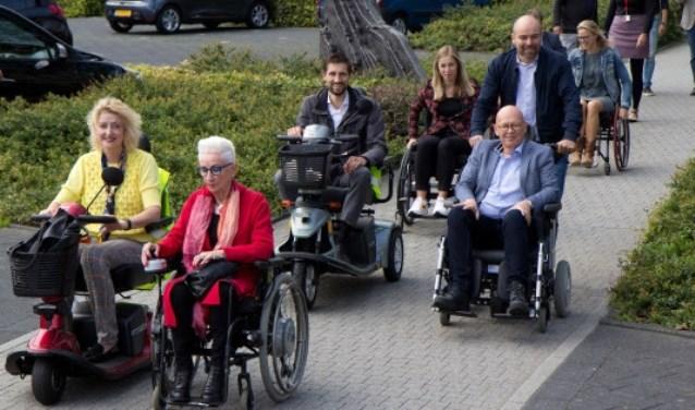 Emmy den Heijer (roze vest) en het college ervaren zelf de bereikbaarheid van de binnenstad met scootmobiel of rolstoel