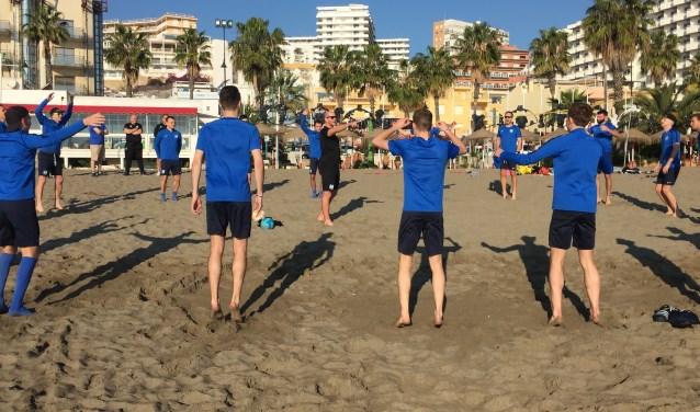 Warming up selectie SDC Putten met keeperstrainer Bas Goettsch voor het voetvolley op het strand van Torremolinos.