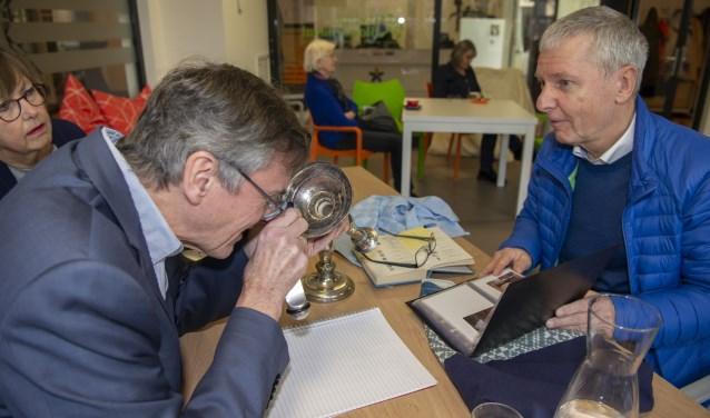 Cees Broekhof bekijkt een zilveren kandelaar met behulp van een loep